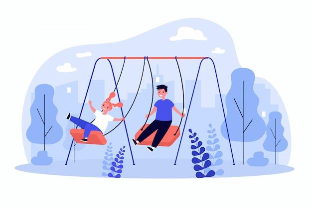 Enfants mignons se balançant, appréciant et riant