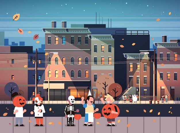 Enfants portant des costumes de monstres marchant nuit ville fond