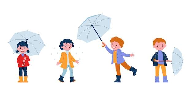 Enfants souriants mignons avec des parapluies dans des bottes en caoutchouc