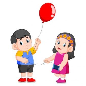 Les enfants tiennent la corde pour le ballon rouge