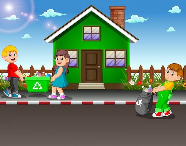Enfants volontaires ramassant des ordures dans la rue de la maison