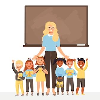 Enseignante et groupe d'enfants se tiennent au tableau noir.