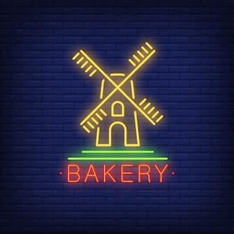Enseigne au néon de boulangerie. moulin à vent jaune sur le mur de briques. nuit lumineuse