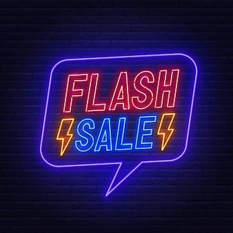 Enseigne au néon de vente flash sur mur de briques.