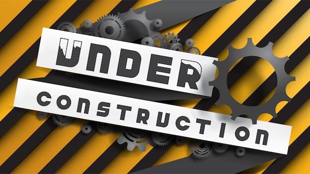 Enseigne under construction décorée par des engrenages noirs et des rouages sur des rayures jaunes noires