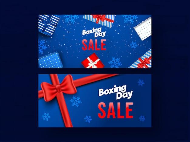 Ensemble de bannière boxing day sale sertie de boîtes-cadeaux vue de dessus et de flocons de neige décorés sur bleu