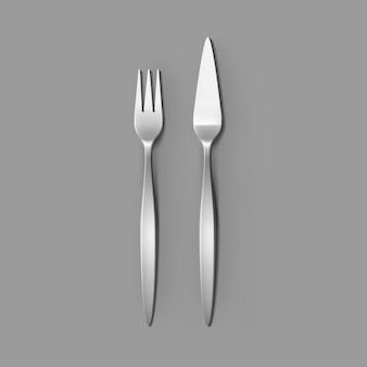 Ensemble de couverts de fourchette à poisson argenté et couteau à poisson isolé, vue de dessus