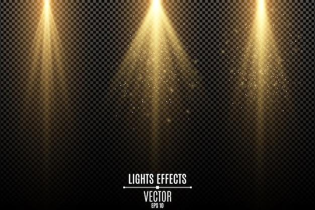 Ensemble d'effets de lumières dorées isolés sur un fond transparent sombre. rayons dorés avec des poussières magiques volantes.
