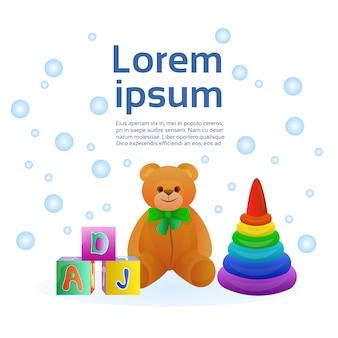 Ensemble de jouets pour bébé d'objets colorés, pyramide, blocs et ours en peluche. modèle de texte
