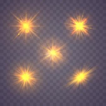 Ensemble de lumière rougeoyante en or jaune explose sur un fond transparent. des particules de poussière magiques étincelantes. bright star soleil brillant transparent, flash lumineux. éclater de poussière et d'éclat isolé.