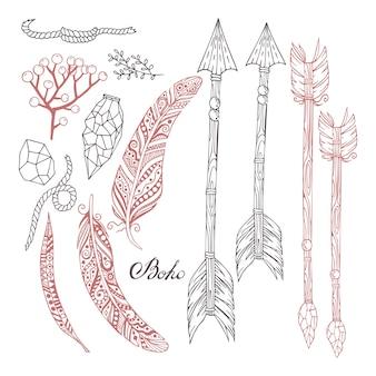 Ensemble peint à la main dans le style boho avec des flèches, des plumes, des plantes, des pierres et une corde.