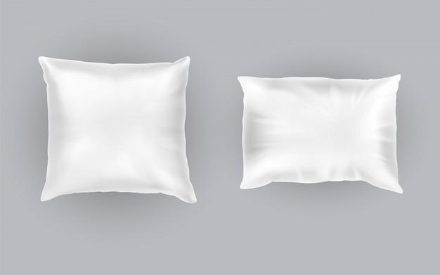 Ensemble réaliste de deux oreillers blancs, carrés et rectangulaires, doux et propre