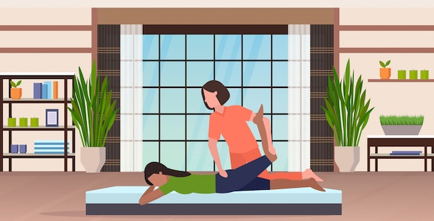 Entraîneur personnel faisant des exercices d'étirement avec une fille instructeur de conditionnement physique aidant la femme à étirer les muscles concept d'entraînement moderne studio de yoga intérieur horizontal pleine longueur