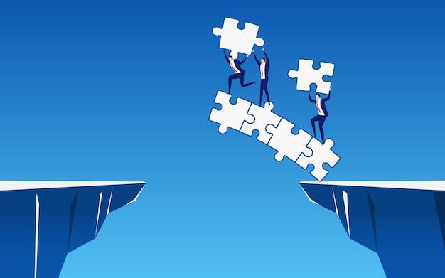 L'équipe d'affaires construit un pont de puzzle pour traverser la colline