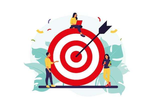 L'équipe commerciale atteint l'objectif. les gens s'approchent d'une énorme cible avec une flèche.