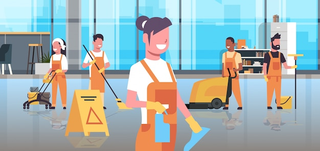 Équipe de concierges service de nettoyage équipe de nettoyeurs en uniforme travaillant ensemble avec un équipement professionnel centre de co-working moderne intérieur de bureau