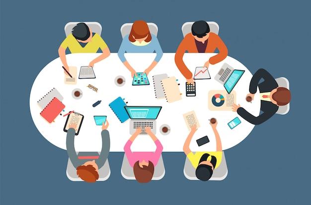 Équipe dirigée en réunion de bureau en vue de dessus de table