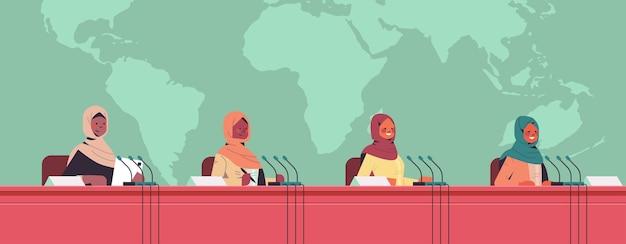 Équipe de femmes médecins arabes donnant un discours à la tribune avec microphone sur la médecine conférence médicale concept de soins de santé carte du monde fond illustration portrait horizontal