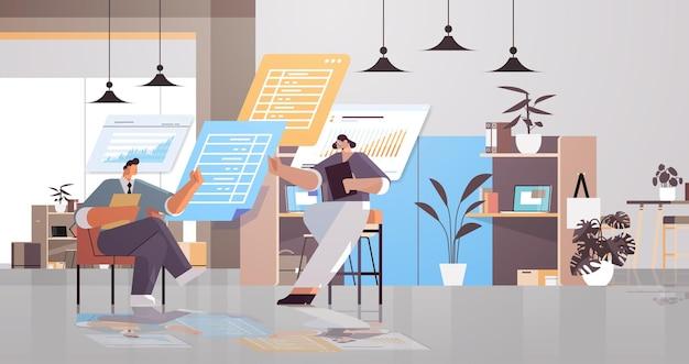 Équipe d'hommes d'affaires analysant les données statistiques sur les tableaux virtuels travail d'équipe réussi