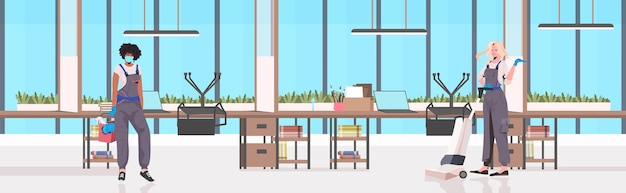L'équipe de nettoyeurs professionnels mix race concierges avec équipement de nettoyage travaillant ensemble horizontal intérieur de bureau
