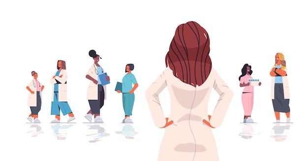 Équipe de professionnels de la santé mélange race femmes médecins en uniforme travaillant ensemble médecine concept de soins de santé illustration vectorielle pleine longueur horizontale