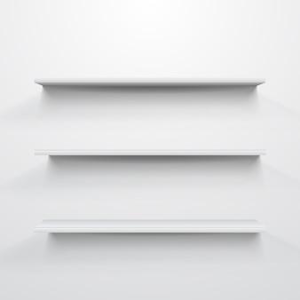 Étagères blanches vides sur fond gris clair.