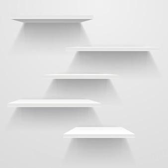 Étagères vides blanches sur un mur blanc.