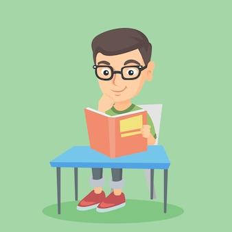Étudiant assis à la table et lisant un livre.
