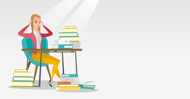 Étudiant assis à la table avec des piles de livres.