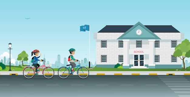 Les étudiants masculins et féminins font du vélo à l'école