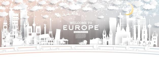 Europe city skyline dans un style papier découpé avec des flocons de neige, la lune et la guirlande au néon. illustration vectorielle. concept de noël et du nouvel an. père noël en traîneau.