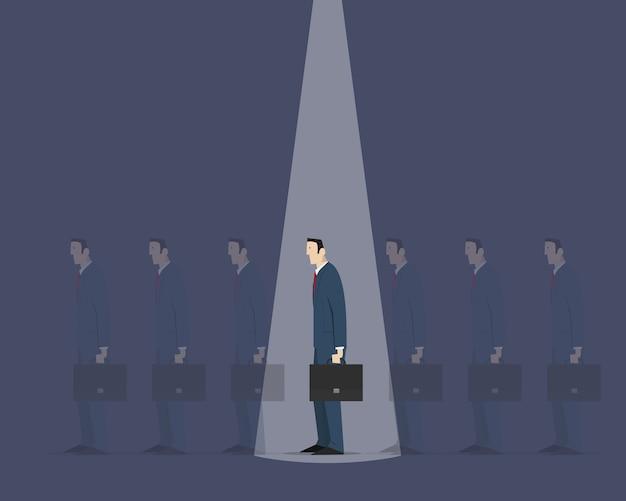 Faisceau lumineux d'en haut choisissant la bonne personne parmi un groupe de boursiers identiques