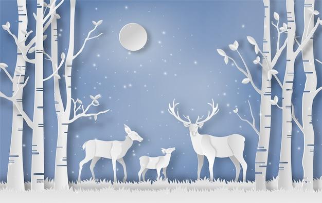 Une famille de cerfs se promène dans une forêt en hiver.