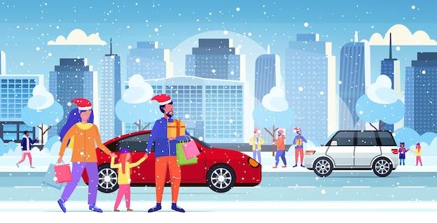 Famille en chapeaux de père noël transportant des sacs à provisions et boîte cadeau de noël nouvel an vacances