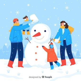 Famille faisant ensemble un bonhomme de neige