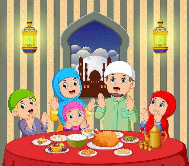 Une famille heureuse prie avant de manger dans sa maison avec une vue magnifique depuis la fenêtre