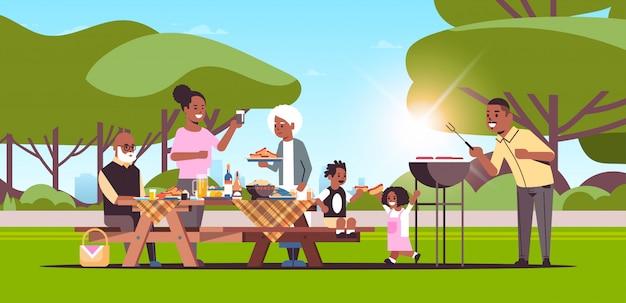 Famille multi génération préparant des hot-dogs sur grill pique-nique barbecue party concept summer park paysage fond plat pleine longueur
