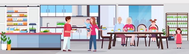 Famille de plusieurs générations ayant le petit déjeuner les gens fixant la table à manger cuisine moderne intérieur des plantes intelligentes de plus en plus concept système plat horizontal pleine longueur