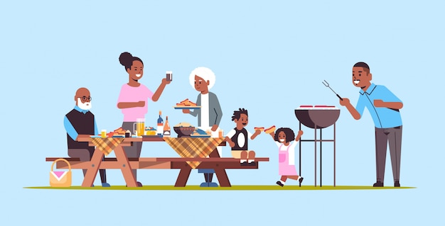 Famille de plusieurs générations préparant des hot-dogs sur grill grands-parents afro-américains parents et enfants s'amusant pique-nique barbecue party concept fond bleu plat pleine longueur horizontale