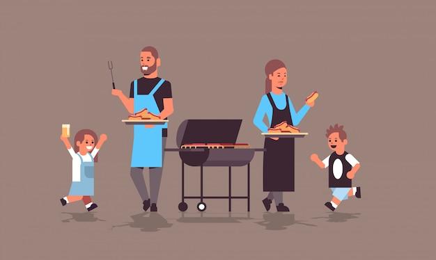 Famille préparer des hot-dogs sur le gril heureux parents et enfants s'amusant pique-nique barbecue party concept télévision horizontale pleine longueur