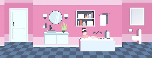 Fat obese woman washing relaxant dans le bain avec de la mousse en surpoids fille allongée dans la baignoire obésité concept salle de bain moderne intérieur pleine longueur