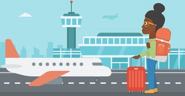Femme à l'aéroport avec valise.