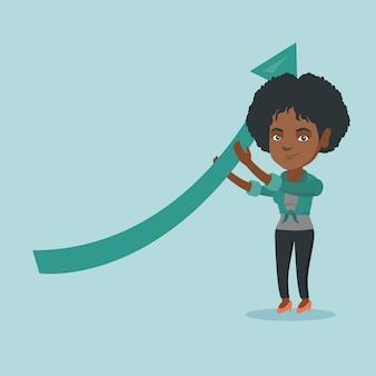 Femme d'affaires africaine tenant la flèche qui monte.