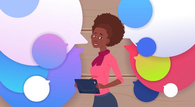 Femme d'affaires afro-américaine tenant une tablette parlent plus de bulles de chat colorées