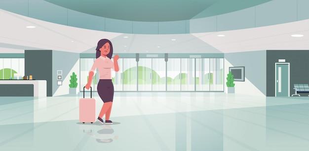 Femme affaires, à, bagage, moderne, réception, femme affaires, tenue, valise, girl, debout, dans, hall, contemporain, hôtel, hall, intérieur