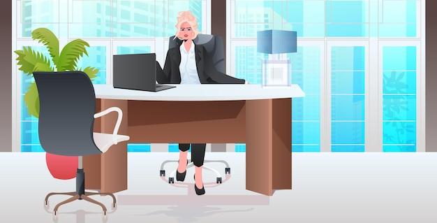 Femme d'affaires blonde assise au travail de chef de femme d'affaires travaillant au bureau horizontal