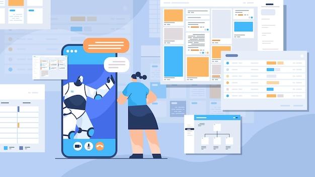 Femme d'affaires discutant avec un robot sur l'écran du smartphone lors d'un appel vidéo