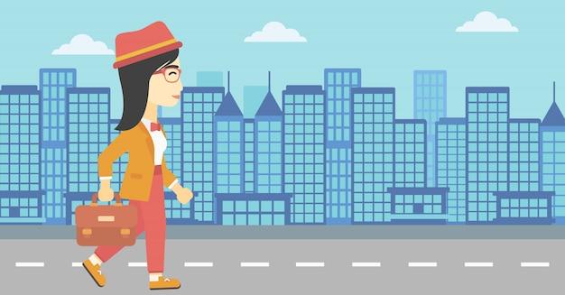 Femme d'affaires réussie à pied avec mallette.
