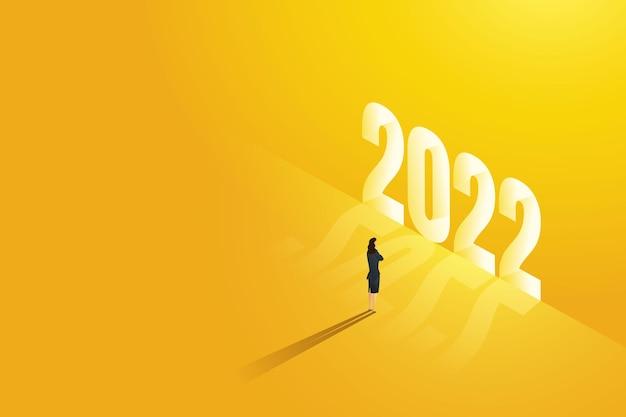 Une femme d'affaires se tient devant un brillant brillant en 2022