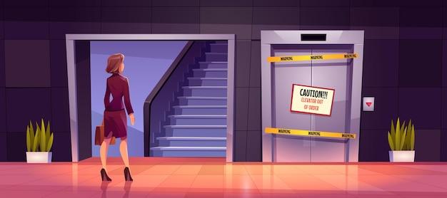 La femme d'affaires se tient près de l'échelle et de l'ascenseur cassé